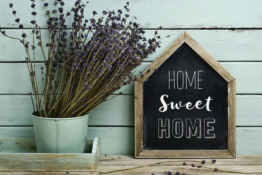 closeup of a house-shaped chalkboard with the text home sweet home written in it and a bunch of lavender flowers in a flower pot, against a rustic pale blue background