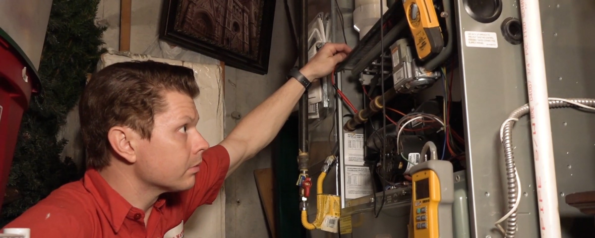 Jon Wayne heating technician working on a furnace