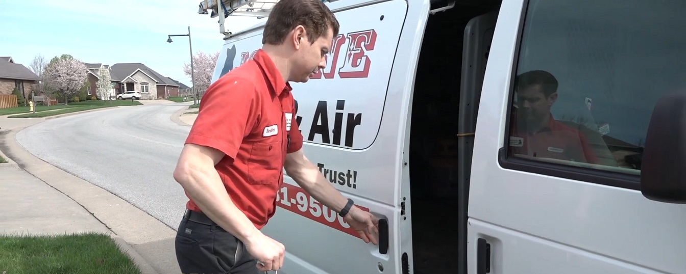 Jon Wayne Heating & Air technician opening van parked inside a neighborhood in Springfield Missouri