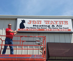 Owner of Jon Wayne Heating & Air with sign on building decades ago