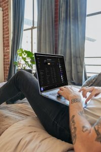 Guy working from home on his bed